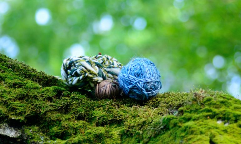 Wool yarns on a mossy birch