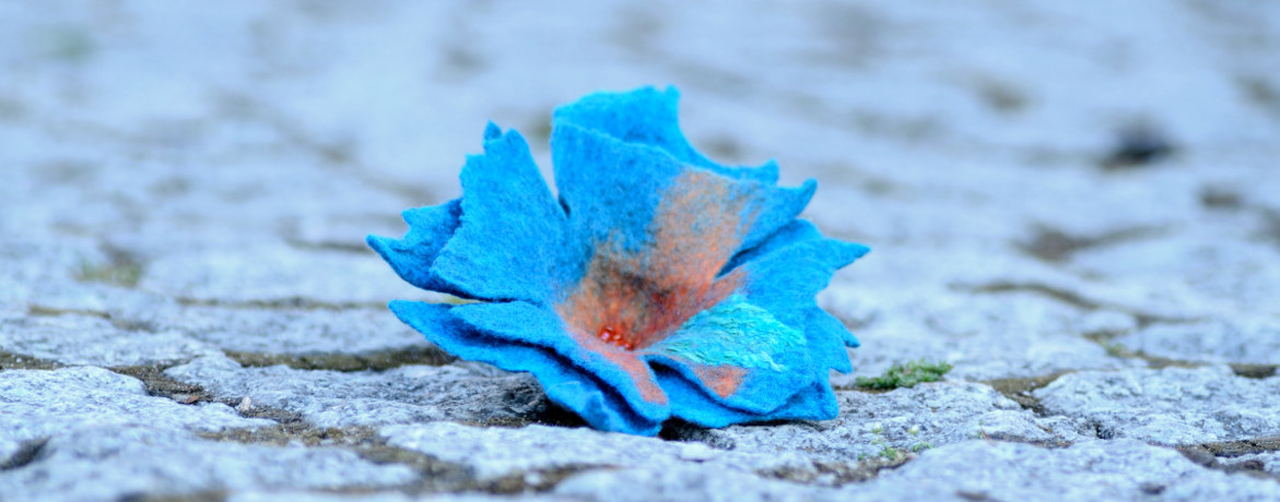 Blue felt brooch on a paving stones